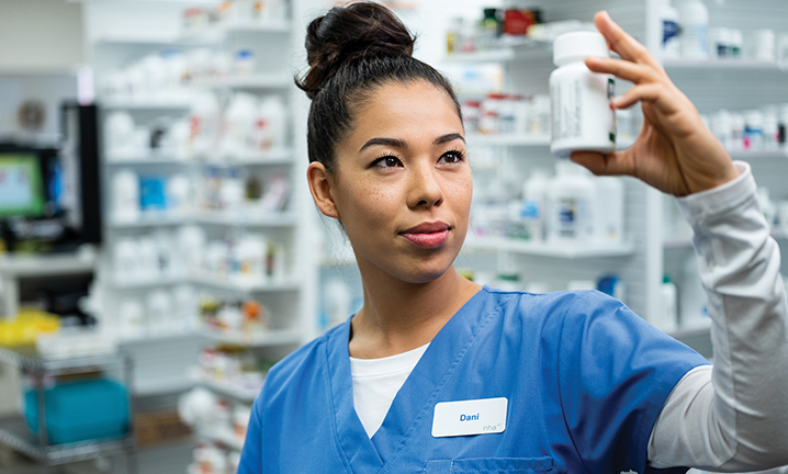 pharmacy-technician-checking-perscription-on-customers-pill-bottle